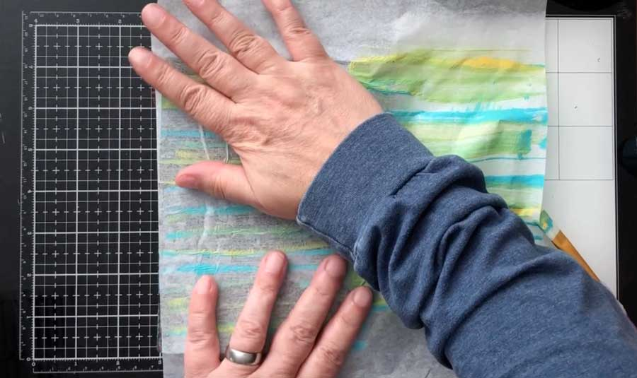 Rub tissue paper with hands putting paint on tissue paper