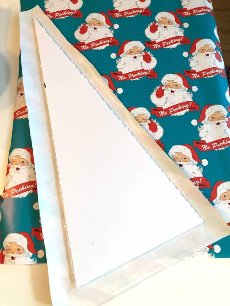 3. Use Glue To Stick The Paper On... Cover one side of the Christmas tree with glue (I used Mod Podge) and then press it onto the wrapping paper, smushing it down to make it stick.