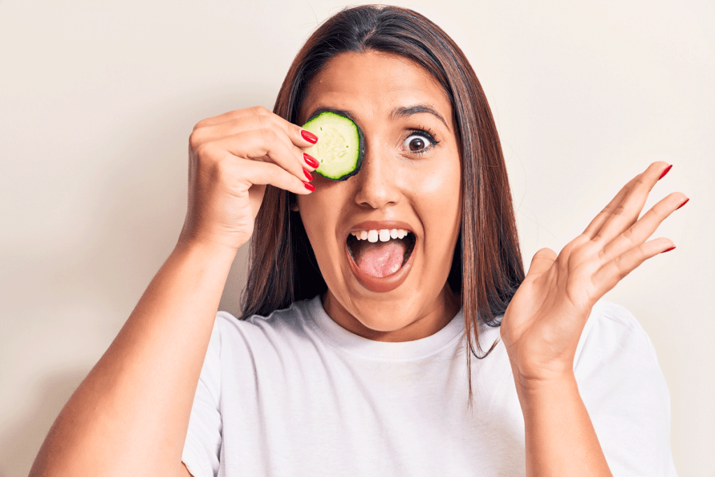 Woman with cucumber slice over eye, natural remedies for eye bags
